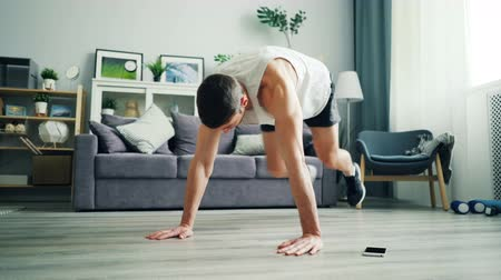 plankenvloer : Strong young man in sportswear is doing cardiovascular exercises in plank position practising alone using smartphone. Domestic sports and modern technology concept.