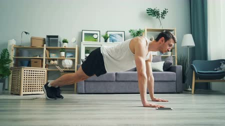 plankenvloer : Serious young sportsman is touching screen of smartphone then practising plank position on wooden floor in house. Active youth and modern technology concept.