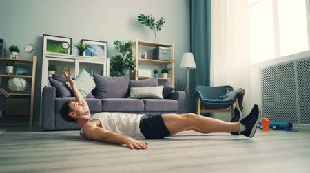 laminát : Active guy student is exercising at home doing sports lying on floor raising legs and arms building abdomen muscles. Healthy lifestyle, apartment and youth concept.
