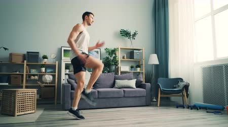 move well : Active male sportsman is doing cardio exercises at home raising legs working out alone enjoying physical activity. Healthy young people, apartment and modern lifestyle concept. Stock Footage