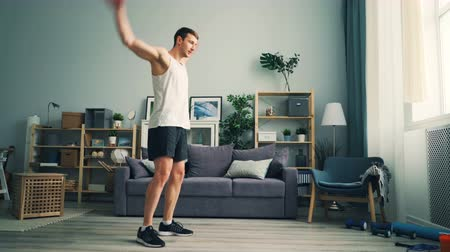 move well : Good-looking sportsman in stylish sportswear is exercising at home rotating arms doing physical exercises for shoulders and chest muscles. House and wellness concept. Stock Footage