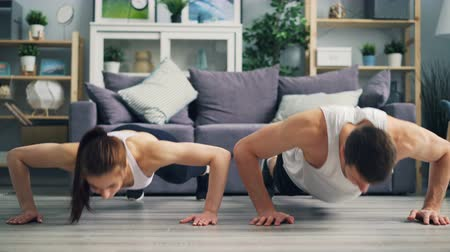 forte : Beautiful couple young girl and guy are exercising together doing pushups and clapping hands at home. People, healthy lifestyle and relationship concept.