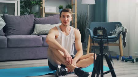 vlogging : Cheerful sportsman in trendy sportswear is recording video for online vlog talking looking at camera gesturing and smiling sitting on bright yoga mat. Stock Footage