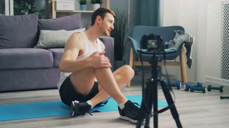 sakk : Sporty male blogger in sports clothes is making video for online blog doing exercises and talking recording with camera. Guy is sitting on yoga mat at home.