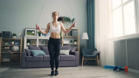 motivováni : Fit female student in trendy sportswear is doing sports at home jumping rope in living room working out alone focused on practice. Millennials and hobby concept.