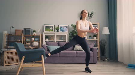 squatting : Beautiful young sportswoman is doing squats at home using armchair training body pumping muscles. Millennials, active people and interior concept.