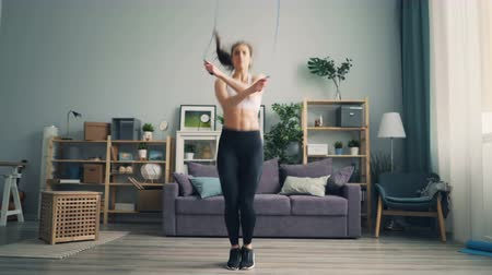 負け : Serious young woman is doing sports exercises jumping rope losing weight in house working out. Modern studio apartment with furniture is visible in background. 動画素材