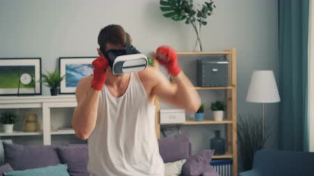 simulace : Young man in modern augmented reality glasses is boxing in apartment training alone at home enjoying contemporary devices and physical activity.