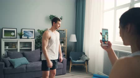 férfiasság : Young woman is recording video of handsome male bodybuilder using smartphone camera. Masculine guy in trendy sportswear is showing muscles posing and talking. Stock mozgókép