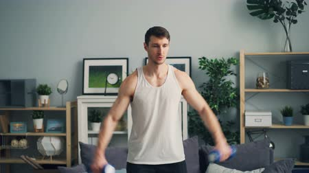 burro : Muscular guy is training with heavy dumb-bells in apartment raising arms breathing focused on lifting weight. Healthy lifestyle and active millennials concept.