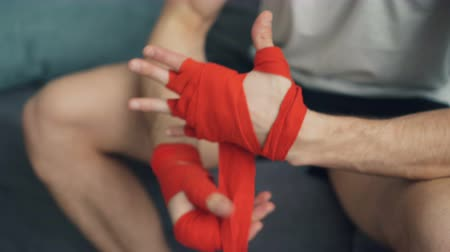férfiasság : Closeup shot of man wrapping hands with protective wrist bandages pulling wraps then clapping hands ready for training. Active lifestyle and sports concept.