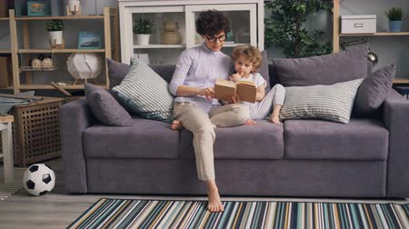 literatuur : Young woman loving mother is reading book to her adorable son sitting on sofa in studio apartment together. Happy family, interior and parenthood concept.