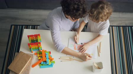 kleurplaten : High angle view of young woman and child drawing together making picture with colored pencils in flat at table. Family, mother and son and hobby concept. Stockvideo