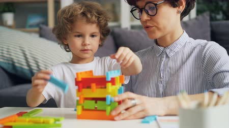 konzentriert : Young woman and her small child are playing with wooden construction blocks at home touching toys concentrated on game. Leisure activity and childhood concept. Videos