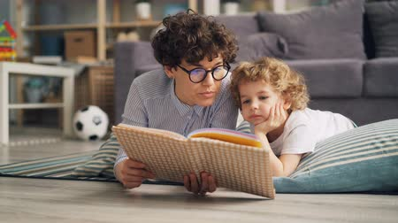 cuidadoso : Young lady is reading book to her son and discussing story lying on floor at home on warm blanket and relaxing. Family activity, happy people and house concept. Vídeos