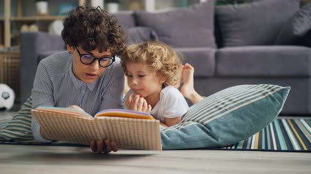 ilginç : Young woman mommy is reading book to curious boy discussing story lying on floor at home and enjoying leisure time and childrens literature. House and hobby concept. Stok Video