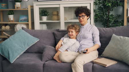 ilginç : Mother and little son are watching TV at home talking and smiling sitting on sofa together enjoying cartoons. Modern technology and childhood concept. Stok Video