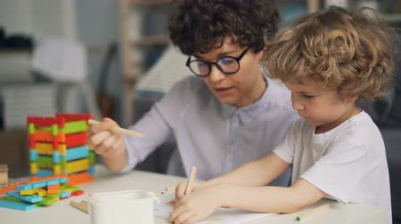 kleurplaten : Adorable small child is drawing picture with pencils while proud mother is talking and smiling enjoying her sons talent. Childhood and parenthood concept. Stockvideo