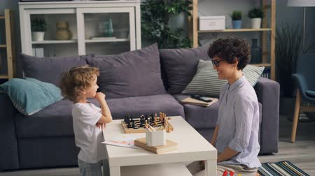 babysitter : Young woman and happy little boy are playing chess at home then doing high-five celebrating victory. Family activities, happiness and lifestyle concept.