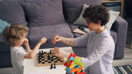enjoyable : Cute child is learning to play chess and having fun with cheerful young mother in apartment. Leisure activities, happy people and family time together concept.
