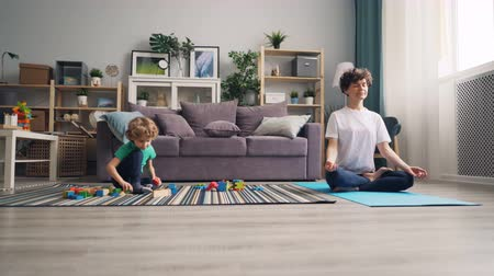 sakk : Small child is playing with blocks on floor while his young mommy meditating in lotus position on yoga mat. Relaxation, childhood and family house concept.