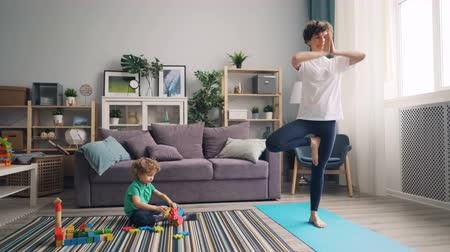 flexibilidade : Young woman is practising yoga at home while calm child is playing with toys on floor. Beautiful apartment with furniture and plants is in background.