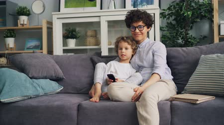 family watching tv : Happy child is watching TV with loving mother at home on sofa holding remote control embracing and laughing. Happiness, family and modern technology concept.