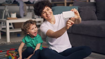 заботливый : Young mother and little son are taking selfie with smartphone camera in apartment posing and smiling, boy is holding bright toy. Photos and family concept.