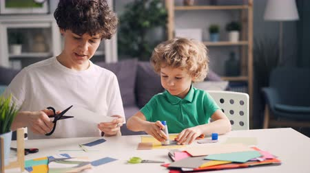 schrijfwaren : Mother and son are doing collages cutting paper with scissors and sticking figures with glue sitting at table together. Creative people and childhood activities concept. Stockvideo