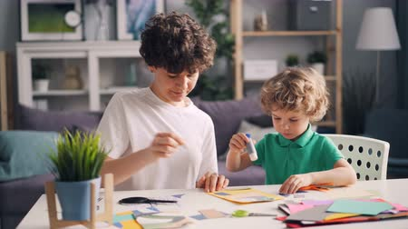 papírnictví : Little boy and his mom are making collage cutting paper figures sticking with glue enjoying creative activity. Family hobby, leisure time and apartment concept.