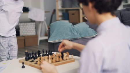 enjoyable : Joyful boy is having fun with chess pieces while caring mom is teaching him to play game at home at table. Intelligent sports and happy childhood concept.