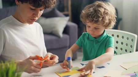 caring : Young lady professional designeer is teaching her son to make collages using paper, glue stick and scissors working at home at table. People, family and art concept. Stock Footage