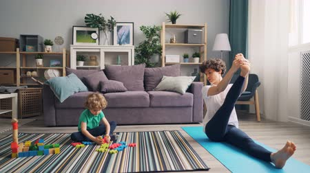blocks of flats : Cute boy is playing with toys on floor while cheerful mother is doing yoga on mat at home relaxing and enjoying leisure time. Healthy lifestyle and familly concept.