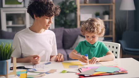 babysitter : Creative family mom and small child are doing collages with colored paper, scissors and glue stick. People are talking smiling creating beautiful design. Stock Footage