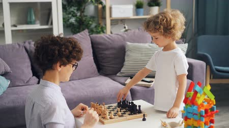 érdekes : Small boy and his intelligent mother are playing chess at home and talking discussing interesting game during leisure time. Family traditions and childhood concept.