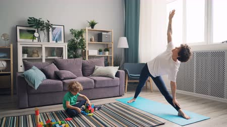 sport dzieci : Beautiful girl mother is doing yoga balancing and stretching when adorable kid is playing with toys on floor in morning. Family and healthy lifestyle concept.
