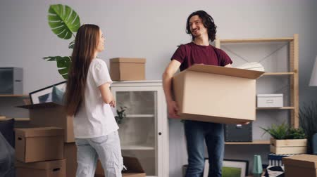 coming home : Young man and woman are bringing things in boxes to new apartment and kissing looking around happily. Relocation, modern youth and beautiful interior concept.