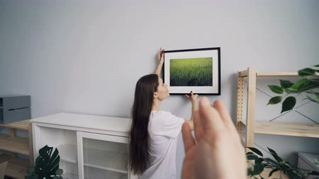 relocate : Pretty girl is hanging picture on wall in new apartment while man is choosing place gesturing making frame with hands then showing thumbs-up approving choice.
