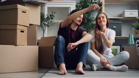 szállás : Young man house owner is giving keys to attractive girlfriend then kissing her relaxing on floor with boxes and talking. Youth, moving in together and relocation concept. Stock mozgókép