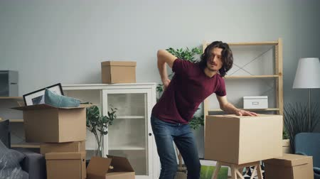 coming home : Tired guy is bringing heavy boxes in room suffering from backache touching back with unhappy face during relocation. Sick people and apartments concept.