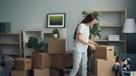 relocate : Young attractive girl and guy are carrying things in carton boxes during relocation in new apartment talking and smiling. People, house and lifestyle concept.