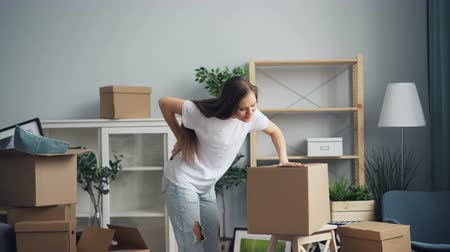 housing problems : Tired girl is bringing heavy boxes then touching back suffering from backache during moving to new house. Relocation, young women and problem concept.