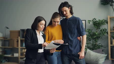 szállás : Real estate agent is showing legal documents to man and woman, young people are talking and reading discussing deal standing indoors in apartment together.