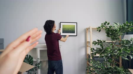 obrázky : Woman is helping handsome guy to choose place for beautiful picture in light room gesturing and talking. Young couple is decorating flat after relocation.