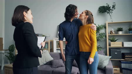 szállás : Housing agent is giving keys to buyers of new apartment, happy husband and wife are hugging and kissing, man is shaking hands with female realtor.