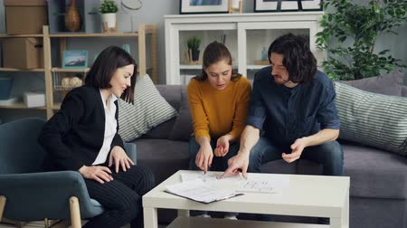 szállás : Girl and guy are looking at flat plans and talking to realtor sitting at table indoors having business conversation. Modern accommodation, youth and house concept.