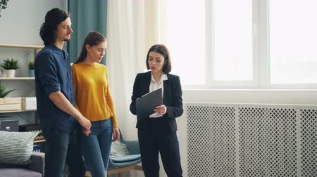 domande e risposte : Husband and wife are talking to housing agent cheerful young lady looking at documents and new apartment. Real estate business and modern youth concept.