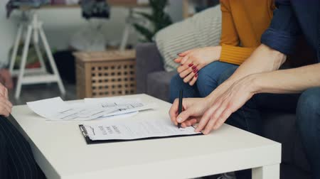 assinatura : Close-up of guy signing contract buying house then taking key from housing agent and shaking hands sitting at table indoors. Business and apartment concept.