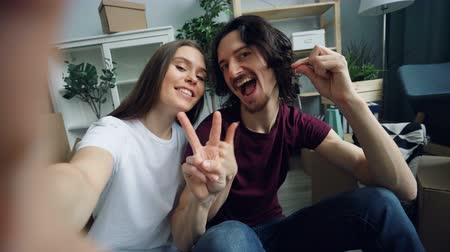 szállás : POV shot of cute young couple taking selfie at home with new house keys showing thumbs-up and smiling looking at camera. People, relocation and housing concept.