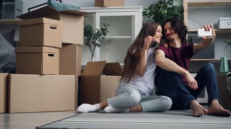 szállás : Happy couple is taking selfie with keys kissing and talking holding smartphone in new apartment. Relocation, relationship and modern technology concept.